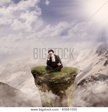 Businessman Working With Laptop On A Rock