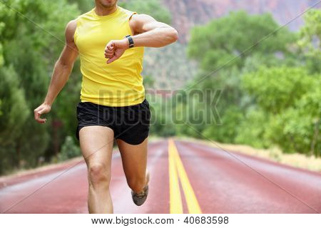 Runner with heart rate monitor sports watch. Man running looking at his pulse outside in nature on road.