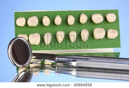 Set of dental tools with denture on blue background
