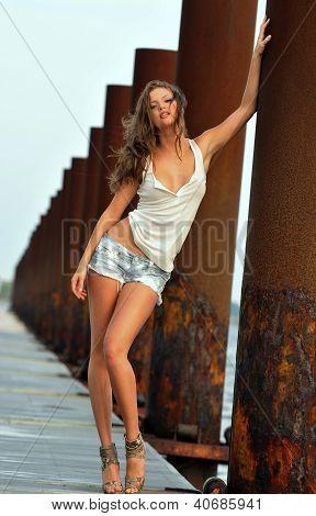 Beautiful sexy woman posing in jeans shorts at rusty boat marina