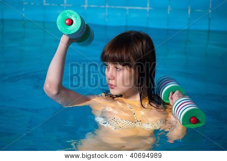 Pretty girl doing aqua aerobic exercise