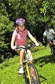 stock photo of young girls  - Teenage girl and her father riding bicycles in summer park - JPG