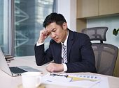 stock photo of frustrated  - Asian businessman sitting and thinking in office - JPG