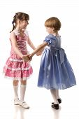 pic of holding hands  - two beautiful little girls in dresses holding hands and dancing isolated on white - JPG