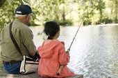 stock photo of grandpa  - A young girl is fishing with her grandpa on a warm summer day - JPG