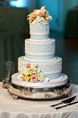 image of three tier  - three tiered blue and white wedding cake with confectionery roses - JPG