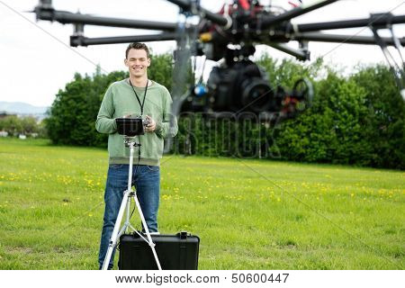 UAV helicopter flying while happy young engineer operating it in background at park