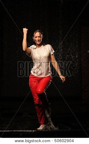 The beautiful girl dancing modern dance in water under rain on a black background