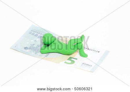 small green plasticine puppet lies on a five euro banknote
