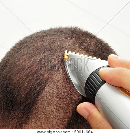 a man man cutting his hair with an electric hair clipper