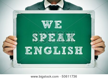 a man wearing a suit holding a chalkboard with the sentence we speak english written in it