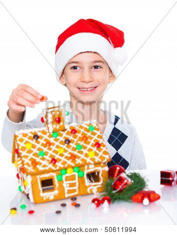 Little boy in Santa's hat with gingerbread house