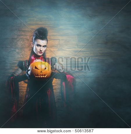 Beautiful, young and sexy female vampire over the smoky background. Halloween concept.