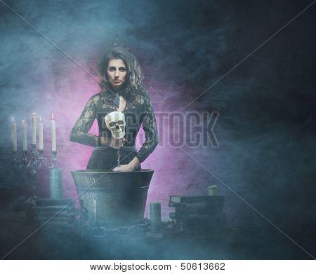 Schöne Hexe machen die Hexerei über dem rauchigen Hintergrund. Halloween Bild.