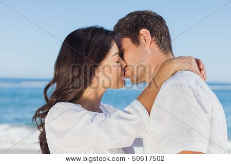 Couple embracing and kissing each other on the beach against ocean