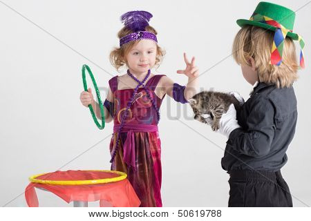 Two children in costumes of magicians show a trick with a kitten, focus on girl