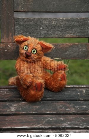 Stuffed Ginger Cat Sitting On Old Wooden Garden Chaiir