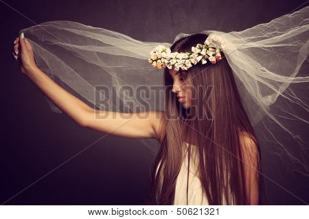 young beautiful woman with veil and wreath of flowers, profile, studio shot