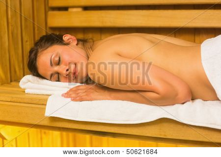 Happy brunette lying down in a sauna and relaxing on white towel