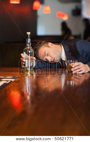 Motionless businessman holding whiskey glass lying on a counter in a classy bar