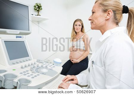 Mid adult gynecologist using ultrasound machine with pregnant woman in background