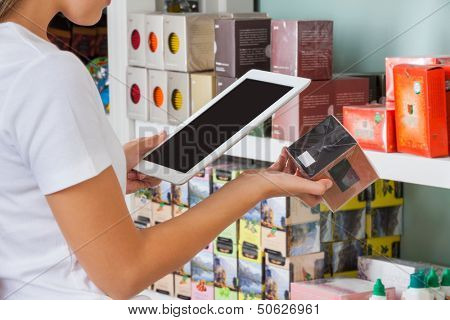 Midsection of young woman scanning barcode through digital tablet at supermarket