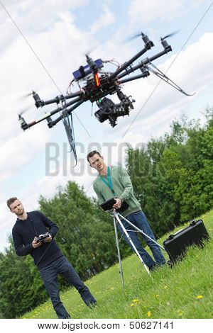 Young engineers flying UAV drone with remote control in park