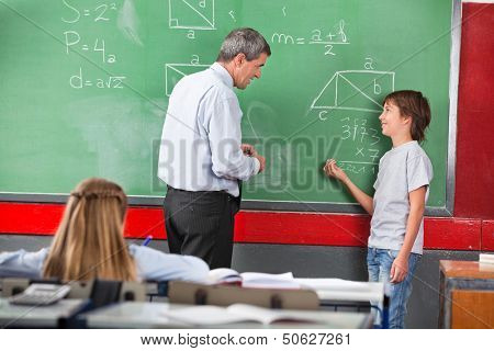 Side view of little schoolboy asking question to teacher while solving mathematics on board in classroom