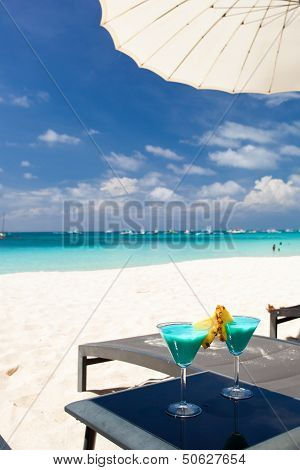 Blue Curacao Cocktail With Slice Of Pineapple On White Beach