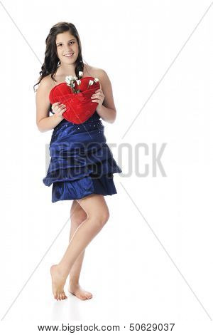 A pretty young teen, barefoot in formal wear,happily holding a red, heart-shaped pillow with a pocketful of white rosebuds.  On a white background.
