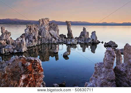 The magic of Mono Lake. Outliers - bizarre limestone calcareous tufa formation on the smooth water of the lake