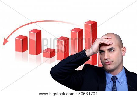 Stressed businessman standing by bar chart