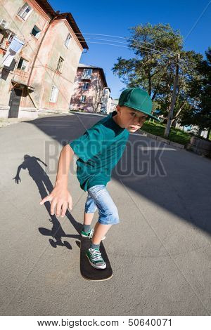 Cheerful boy riding a skateboard on the street. Fish-eye lens.