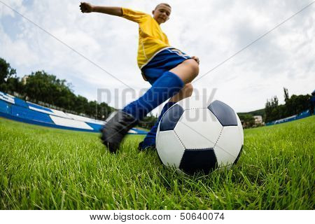 Boy soccer player hits the ball on the football field. Fish-eye lens.