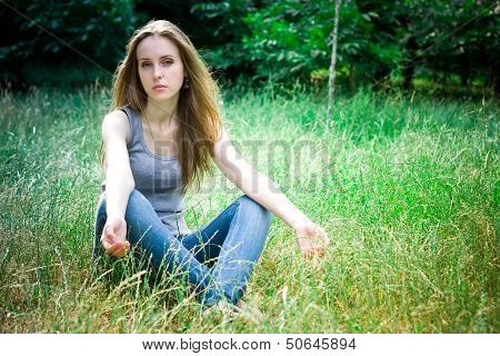 Young Woman Sits And Looks At Camera