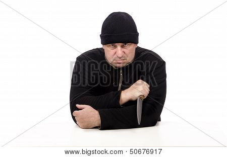 Bandit In Black Clothes Sits And Threatening With Big Knife