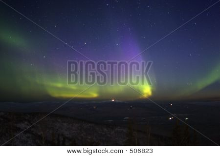 Purple-green-yellowish Northern Lights In Starry Sky Over Hill T