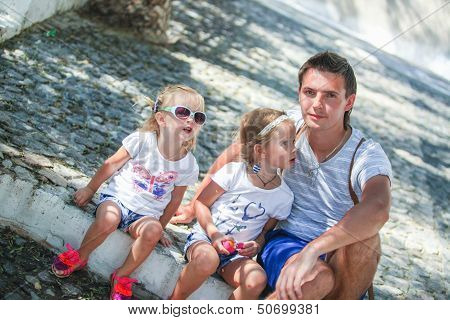 Young Father With Little Daughters Sitting On Street In Old Greek Town
