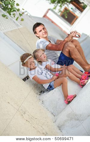 Happy Father And Cute Daughters Sitting On Street In Old Greek Town