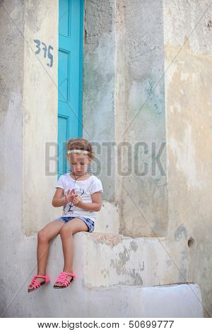 Adorable Little Girl Sitting On The Steps Of Old House In Emporio Village, Santorini, Greece