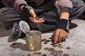 picture of beggar  - Beggar child counting coins sitting on damaged concrete floor  - JPG