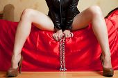 stock photo of sado-masochism  - beautiful young woman sitting on a couch and holding a chain - JPG