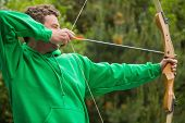 image of shooting-range  - Man in green jumper about to shoot arrow at the archery range - JPG