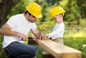 stock photo of daddy  - Little son helping his father with building work - JPG