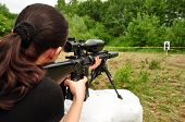 foto of sniper  - Young sniper women training with big gun - JPG