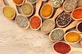 image of flavor  - Assortment of spices in wooden spoons on wooden background - JPG