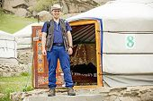 stock photo of yurt  - Man in outdoor clothes in front of the entrance of a Mongolian Yurt - JPG
