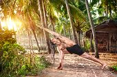 foto of dreadlocks  - Yoga Parivrtta Parsvakonasana horizon pose by fit man with dreadlocks on the beach near the fishermen hut in Varkala Kerala India - JPG