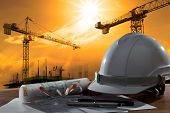 image of construction industry  - file of safety helmet and architect pland on wood table with sunset scene and building construction - JPG