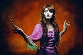 image of faerys  - Witch casts a spell with a magic wand for halloween - JPG